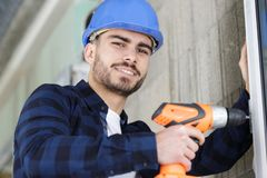 Happy young male holding drill stock photos