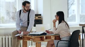 Happy young male manager businessman talking to female boss colleague sitting on table at comfortable modern loft office