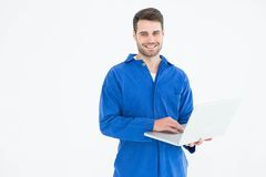 Happy young male mechanic using laptop Stock Images