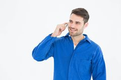 Happy young male mechanic using mobile phone Royalty Free Stock Image
