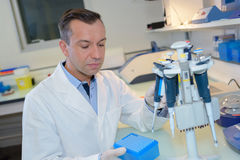 Happy young male researcher working in lab Stock Photo