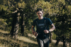 Happy young male runner running through forest Stock Image