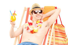 Happy young male sitting on a beach chair and drinking cocktail Royalty Free Stock Image