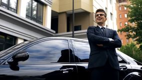 Happy young male standing by new luxurious car, office worker getting promotion stock photo