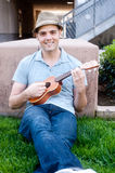 Young male student with ukulele. Happy young male student on campus with ukulele Royalty Free Stock Photos