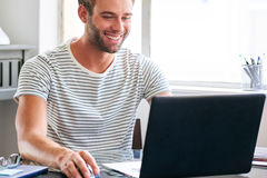 Happy young male student smiling while seated behind his laptop. Handsome young caucasian student smiling while seated at his desk at home busy using his Stock Photos