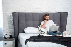 Happy young male using laptop in cozy. Modern bedroom Royalty Free Stock Photos