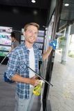 Happy young male worker cleaning window with squeegee. Male Royalty Free Stock Images