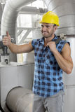 Happy young male worker gesturing thumbs up in industry Royalty Free Stock Photo