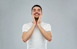 Happy young man applying aftershave to face Stock Photo