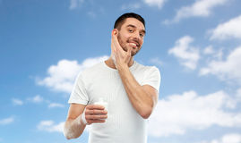 Happy young man applying cream or lotion to face Stock Photography