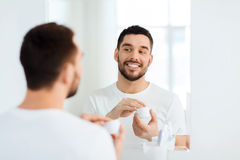 Happy young man applying cream to face at bathroom Royalty Free Stock Images