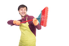 Happy young man with apron and gloves playing with a broom durin Stock Image