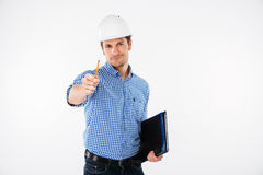 Happy young man architect in hard hat pointing on you. Happy young man architect in hard hat holding folder and pointing on you royalty free stock photography