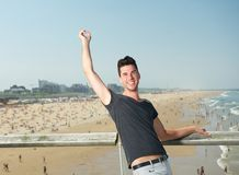 Happy young man with arm raised at the seaside Stock Images