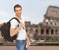 Happy young man with backpack and book travelling royalty free stock images