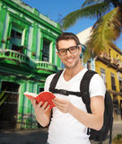 Happy young man with backpack and book travelling Stock Photo