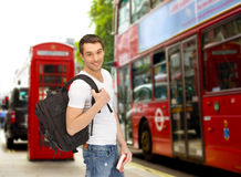 Happy young man with backpack and book travelling Royalty Free Stock Image