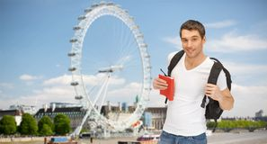 Happy young man with backpack and book travelling Stock Images