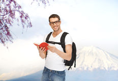 Happy young man with backpack and book travelling. People, travel, tourism, japan and education concept - happy young man in eyeglasses with backpack and book Royalty Free Stock Images
