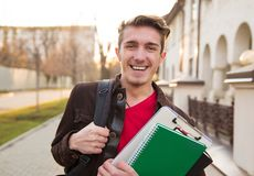 Cheerful man with books walking on street. Happy young man with backpack and college books walking on street and laughing at camera Stock Photo