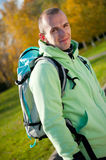 Happy young man with backpack in the park. Royalty Free Stock Image