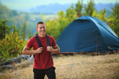 Happy young man backpacker in a summer mountains Royalty Free Stock Photos