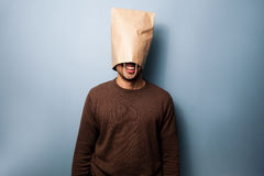 Happy young man with a bag over his head. Happy young man standing with a bag over his head Stock Images