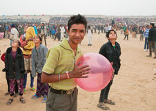 Happy young man with balloon walking in the crowd of people Stock Image