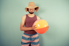 Happy young man with beach ball and sun hat Stock Photography