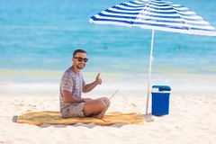 Happy young man in the beach under umbrella near the ocean working on his laptop and showing thumbs up. Happy man in the beach under umbrella near the ocean royalty free stock images