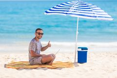 Happy young man in the beach under umbrella near the ocean working on his laptop and showing thumbs up. Happy man in the beach under umbrella near the ocean royalty free stock photos