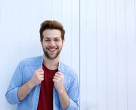 Happy young man with beard against white background. Portrait of a happy young man with beard posing against white background royalty free stock image