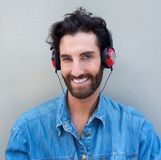 Happy young man with beard listening to music with headphones Royalty Free Stock Images