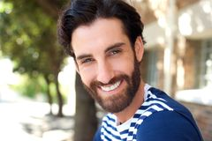 Happy young man with beard smiling outdoors Stock Images