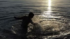 Young man beats the lake water to entertain at sunset in slo-mo. A happy young man beats the lake water with his hand to entertain and to make brilliant splashes stock video footage