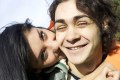 Happy young man being kissed by girlfriend Royalty Free Stock Images