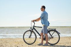 Happy young man with bicycle on beach. People, leisure and lifestyle concept - happy young man with bicycle on beach Royalty Free Stock Photos