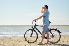 Happy young man with bicycle on beach Royalty Free Stock Photography