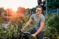 Happy young man with bicycle in park. With glasses for sight at sunset. Royalty Free Stock Image