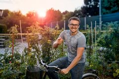 Happy young man with bicycle in park. With glasses for sight at sunset. Royalty Free Stock Photo