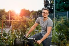 Happy young man with bicycle in park. With glasses for sight at sunset. Stock Images