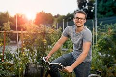 Happy young man with bicycle in park. With glasses for sight at sunset. Stock Photos