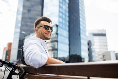 Happy young man with bicycle sitting on city bench Royalty Free Stock Image