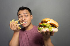 Happy young man bite french fries and holding a burger Royalty Free Stock Photos