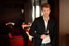 Happy young man in suit holding a glass of wine Royalty Free Stock Photography