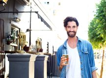 Happy young man in blue shirt holding glass of beer outdoors Stock Images