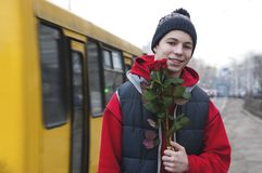 Happy young man with a bouquet of roses on a city street stock photos