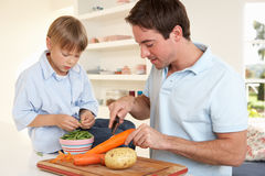 Happy young man with boy peeling vegetables Royalty Free Stock Images