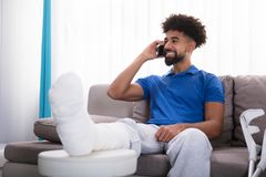 Happy Young Man With Broken Leg Talking On Mobile Phone. Happy Young Man With Broken Leg Sitting On Sofa Talking On Mobile Phone stock images